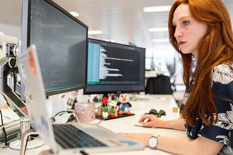 Girl programming on multiple displays